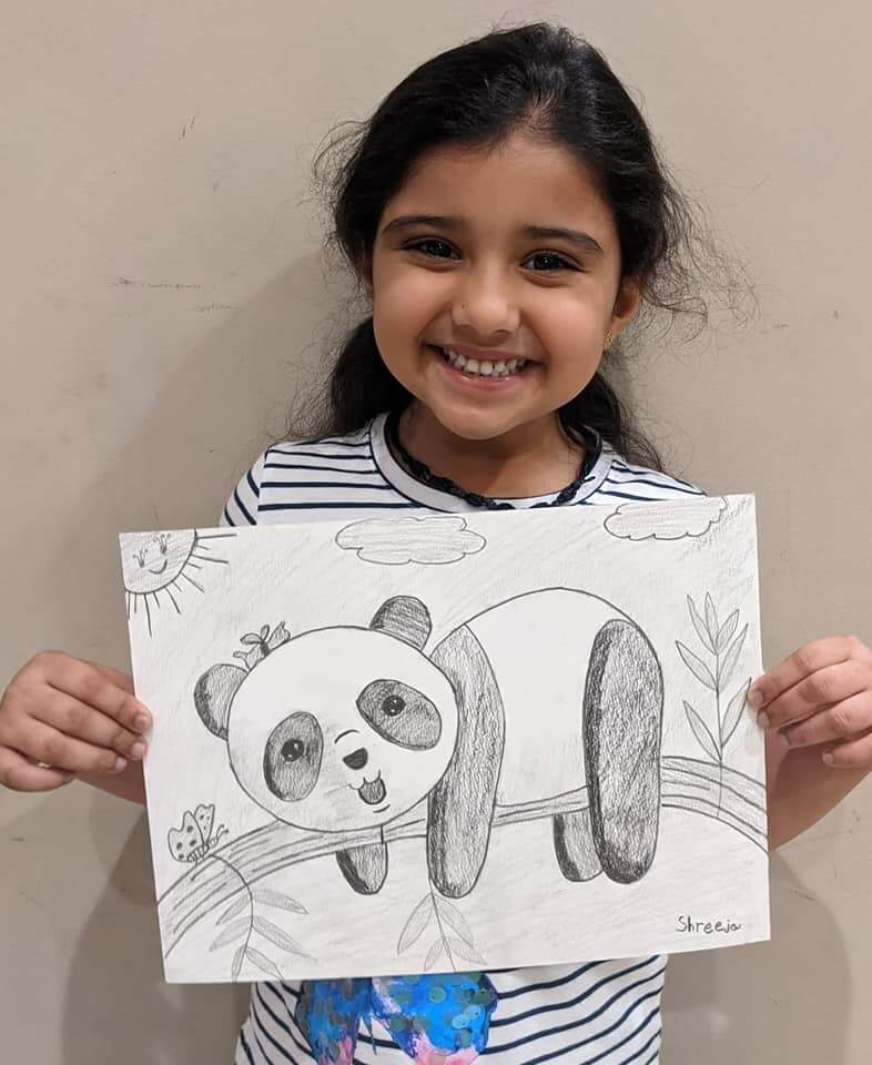 Shreeja pathak is proudly holding the pencil sketch of a cute baby panda which she drew at Nimmy's art classes