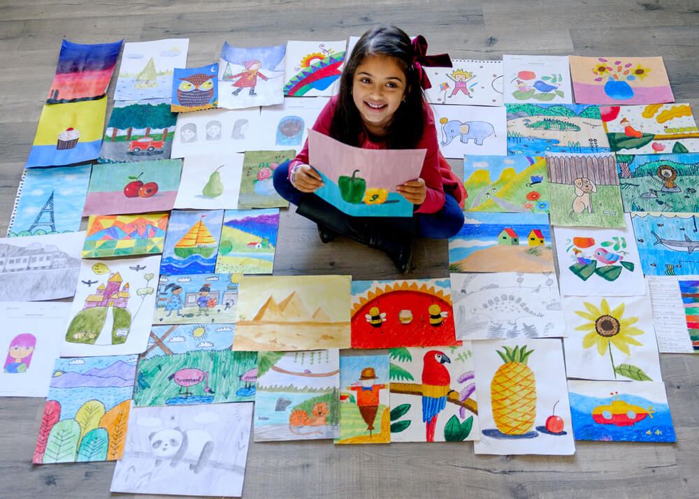 Anika with all her artworks in multiple mediums completed at Nimmy's Art online art classes for kids at Katy, Texas.