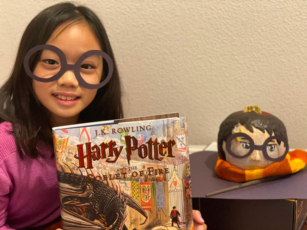 Abigail with her Harry Potter and the Goblet of Fire book, and the Halloween craft that won her the prize at the Halloween Pumpkin Art Contest in her neighborhood.