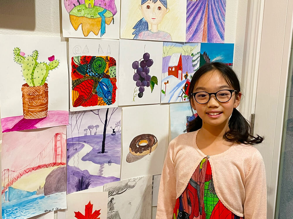 Abigail with a wall art of all her artworks completed at the online classes by Nimmy's Art located in Katy, Texas