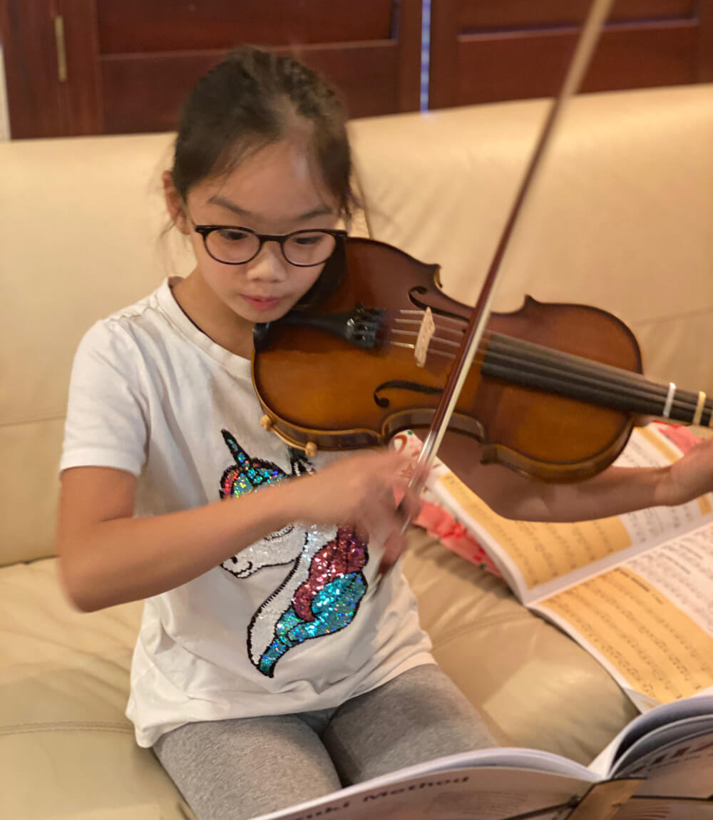 Abigail playing the violin with the help of her notes