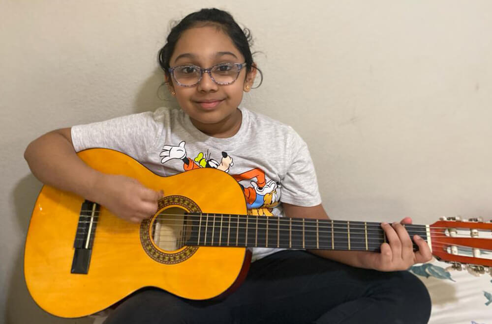 A student at Nimmy's Art playing the guitar during her free time.